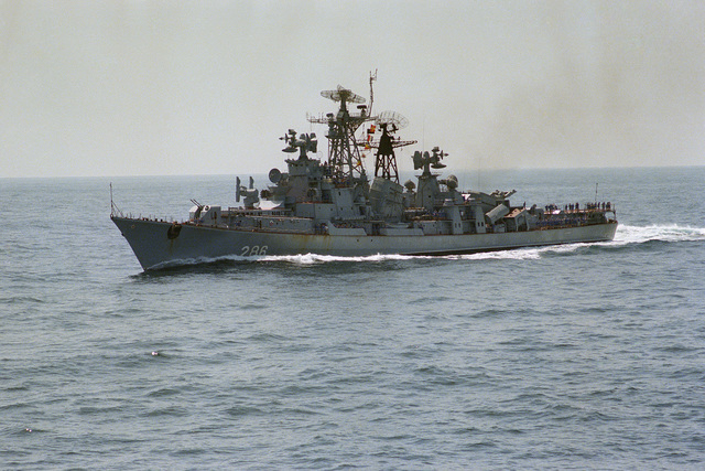 A port bow view of a Soviet Kashin class destroyer passing near the aircraft carrier USS CORAL SEA (CV 43) during her 1979-1980 deployment