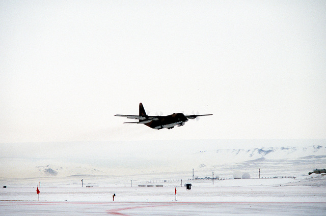 A right front view of a C-130E Hercules aircraft taking off on an airdropping mission. The aircraft is assigned to the 40th Tactical Airlift Squadron, involved in exercise East Arctic '80