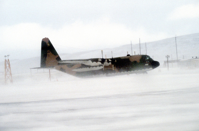 A right side view of a parked C-130E Hercules aircraft, covered by windblown snow. The aircraft is assigned to the 40th Tactical Airlift Squadron, which is involved in exercise East Arctic '80