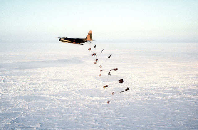 Left rear view of a C-130E Hercules aircraft airdropping petroleum, oil and lubricants containers in the Fram II drop zone. The aircraft is assigned to the 40th Tactical Airlift Squadron, involved in exercise East Arctic '80