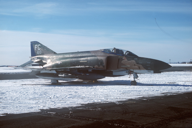 A right front view of an F-4E Phantom II aircraft with auxiliary fuel tanks parked on the flight line.  The aircraft is assigned to the 18th Tactical Fighter Squadron