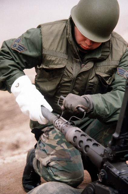A security policeman changes and cleans the hot barrel of an M-2 .50-caliber machine gun during heavy weapons training at Rodriquez Range