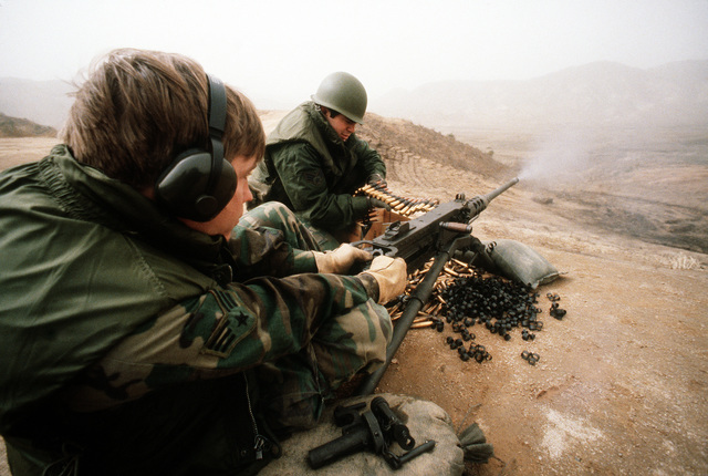A security policeman fires an M-2 .50-caliber machine gun as his teammate feeds the gun with rounds during heavy weapons training at Rodriquez Range