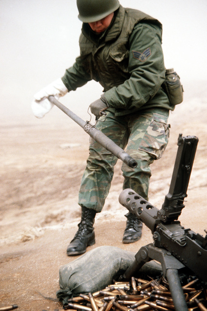 A security policeman removes the hot barrel of an M-2 .50-caliber machine gun for cleaning during heavy weapons training at Rodriquez Range