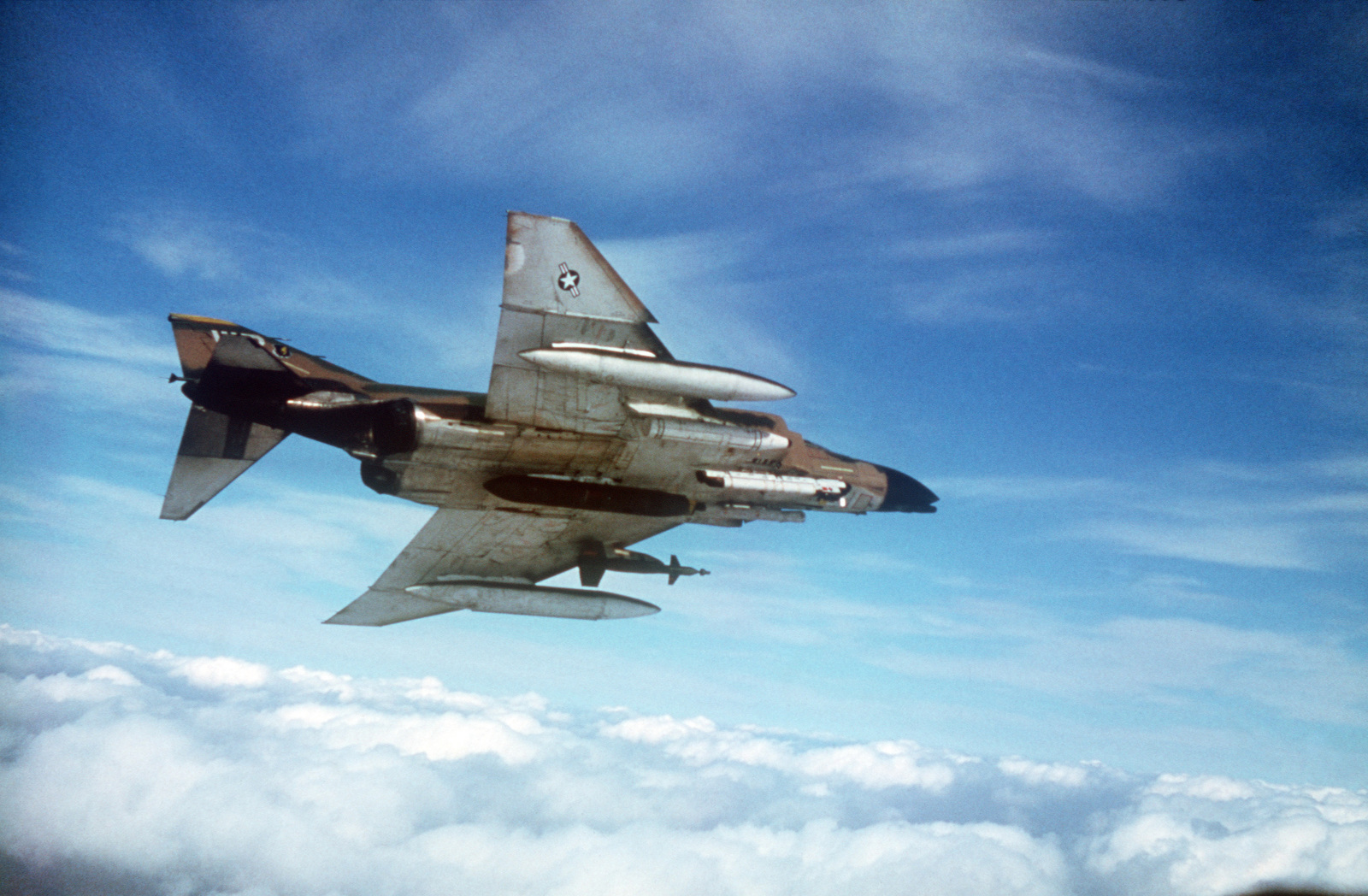 An air-to-air right underside view of an 8th Tactical Fighter Wing F-4D Phantom II aircraft.  The aircraft is equipped with a GBU-12D 500-pound laser-guided bomb, an AN/ALQ-119 electronic countermeasures pod, a Pave Spike laser designator, and a 20 mm gun pod