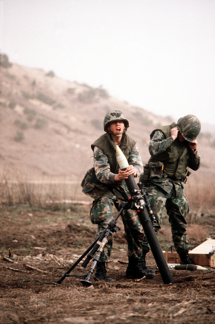 Security policeman SRA Alfred Lerma prepares to drop a white phosphorous mortar into an M-29 81mm mortar during heavy weapons training at Rodriquez Range