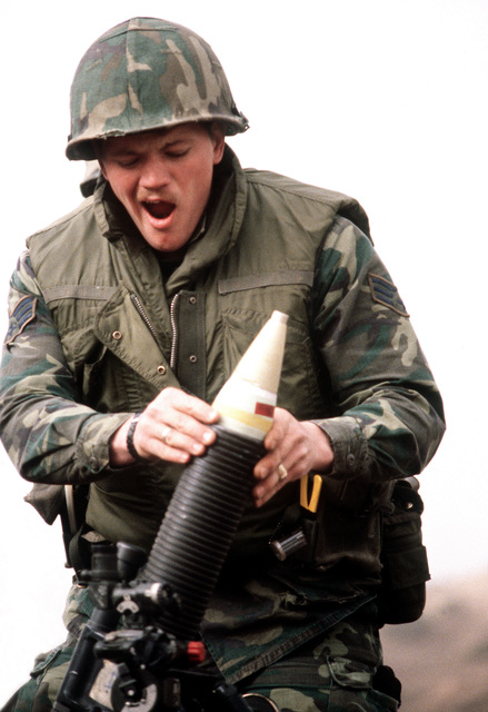 Security policeman SSGT Robert Colyer drops a white phosphorous mortar round into an M-29 81mm mortar during heavy weapons training at Rodriquez Range