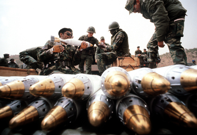 Security policemen set charges on and stack illumination mortar rounds during heavy weapons training at Rodriquez Range