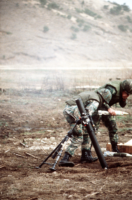 Security policemen take turns dropping rounds into an M-29 81mm mortar during heavy weapons training at Rodriquez Range