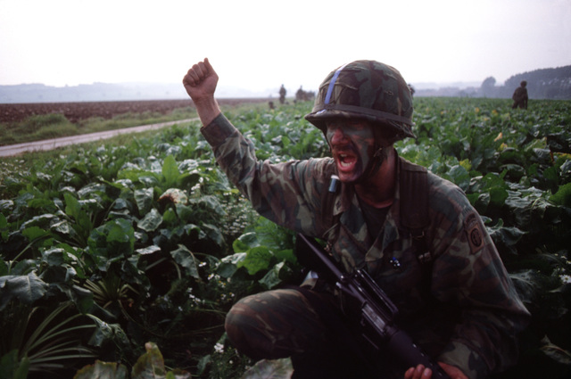 SSGT King yells to the men of his platoon to follow him as they join up near the drop zone and begin the break to their objectives during exercise REFORGER '80