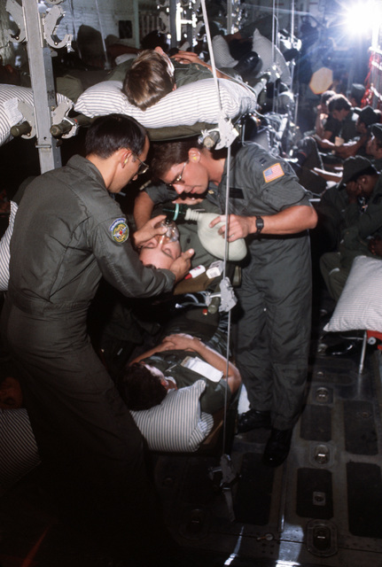 Two members of the 37th Aeromedical Evacuation Group help a patient to breathe during the trip to RAF Lakenheath, England. The men are aboard a C-130 Hercules aircraft