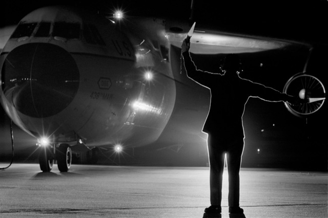 """A ground crewman, using illuminated wands, marshals a C-141 Starlifter aircraft into a parking position. The aircraft, from the 438th Tactical Airlift Wing, is returning troops from exercise Team Spirit '80. Bi-monthly Aerospace Audio Visual Service PHOTO Contest, B&W Entry, Jul. 1980, """"Night Block"""""""