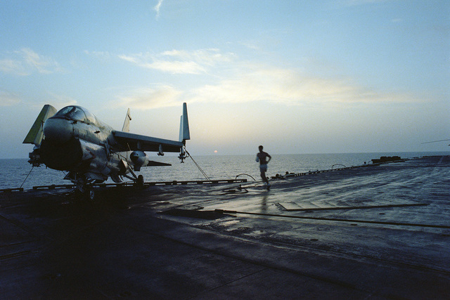 A crewman jogs past a tied down A-7 Corsair II aircraft on the deck of the aircraft carrier USS CORAL SEA (CV 43) on Easter morning