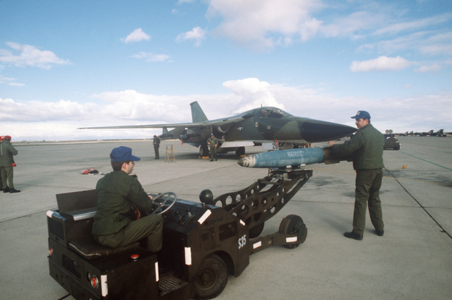 A bomb loader is used to transport a Mark 82 500-pound high drag bomb across the flight line for loading onto an FB-111A aircraft