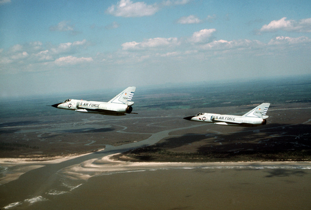 AN air-to-air left side view of two F-106 Delta Dart aircraft over the coast of South Carolina. The aircraft are assigned to the 48th Fighter Interceptor Squadron