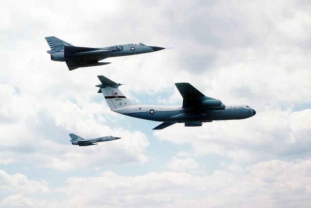AN air-to-air right side view of two F-106 Delta Dart aircraft and a C-141A Starlifter aircraft, leading. The F-106 aircraft are assigned to the 48th Fighter Interceptor Squadron and the C-141A aircraft is assigned to the 437th Military Airlift Wing