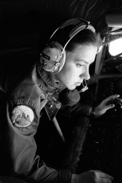 A refueling boom operator, checking her console, aims the refueling boom at an approaching aircraft