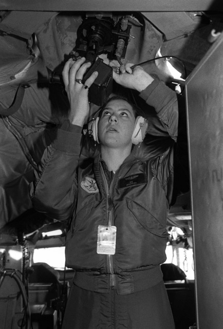 A refueling boom operator checks a sextant for accuracy during preflight mission