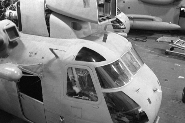 A right front view of an RH-53 Sea Stallion helicopter parked in the hangar bay of the nuclear-powered aircraft carrier USS NIMITZ (CVN-68). The helicopter is being prepared to take part in Operation Evening Light, a rescue mission to Iran