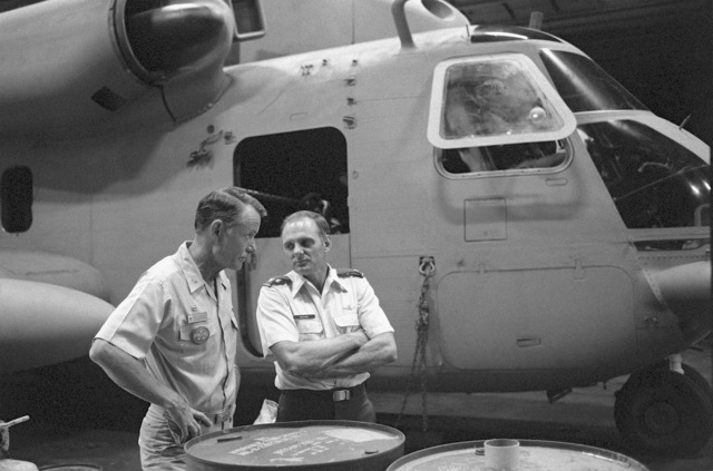 CAPT John R. Batzler, commanding officer of the nuclear-powered aircraft carrier USS NIMITZ (CVN-68), left, and COL Keating, U.S. Air Force, discuss final plans for Operation Evening Light, a rescue mission to Iran. They are standing in front of an RH-53 Sea Stallion helicopter parked in the hangar bay aboard the NIMITZ