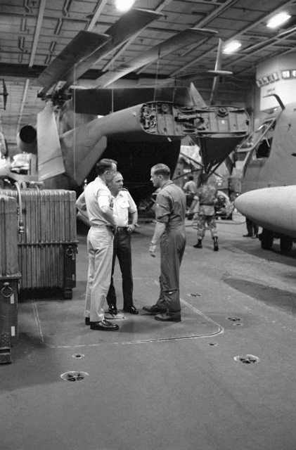 Officers in the hangar bay of the nuclear-powered aircraft carrier USS NIMITZ (CVN-68) discuss final plans for Operation Evening Light, a rescue mission to Iran