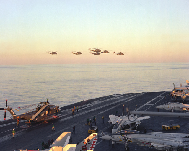 A right side view of six RH-53D Sea Stallion helicopters in flight, just after lifting off the flight deck of the nuclear-powered aircraft carrier USS NIMITZ (CVN-68). The helicopters are taking part in Operation Evening Light, a rescue mission to Iran
