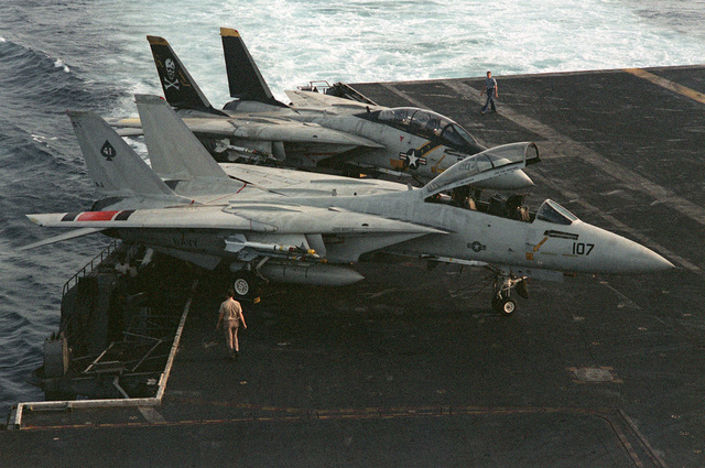 A right side view of two F-14 Tomcat fighter aircraft parked on the flight deck of the nuclear-powered aircraft carrier USS NIMITZ (CVN-68)