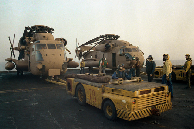 A tow tractor moves an RH-53 Sea Stallion helicopter into position on the flight deck of the nuclear-powered aircraft carrier USS NIMITZ (CVN-68) prior to the start of Operation Evening Light, a rescue mission to Iran