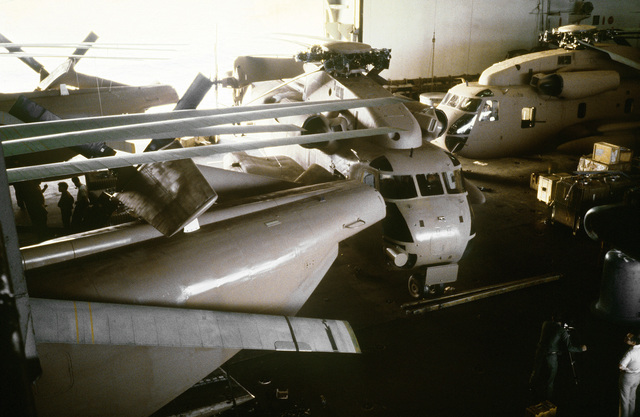 A view of four parked RH-53 Sea Stallion helicopters in the hangar bay aboard the nuclear-powered aircraft carrier USS NIMITZ (CVN-68). The helicopters are being prepared to take part in Operation Evening Light, a rescue mission to Iran