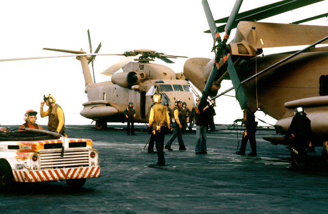 A view of RH-53 Sea Stallion helicopters parked on the flight deck of the nuclear-powered aircraft carrier USS NIMITZ (CVN-68). The helicopters are being prepared for participation in Operation Evening Light, a rescue mission to Iran