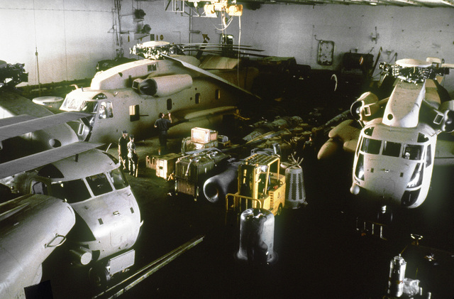 An interior view of the hangar bay aboard the nuclear-powered aircraft carrier USS NIMITZ (CVN-68). The parked RH-53 Sea Stallion helicopters are being readied for Operation Evening Light, a rescue mission to Iran