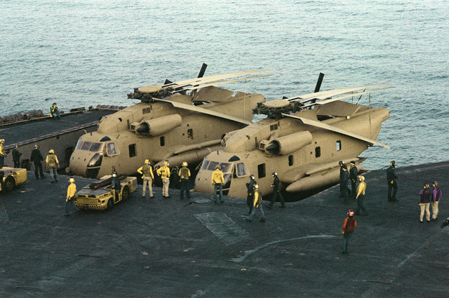 Crewmen aboard the nuclear-powered aircraft carrier USS NIMITZ (CVN-68) prepare two RH-53 Sea Stallion helicopters for participation in Operation Evening Light, a rescue mission to Iran