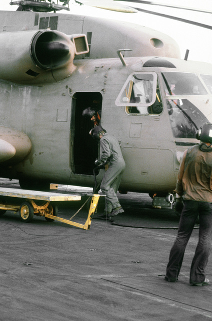 Crewmen board an RH-53 Sea Stallion helicopter on the flight deck of the nuclear-powered aircraft carrier USS NIMITZ (CVN-68) prior to the start of Operation Evening Light, a rescue mission to Iran