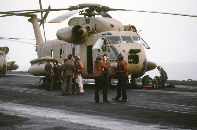 Crewmen gather around an RH-53 Sea Stallion helicopter on the flight deck of the nuclear-powered aircraft carrier USS NIMITZ (CVN-68) prior to the start of Operation Evening Light, a rescue mission to Iran