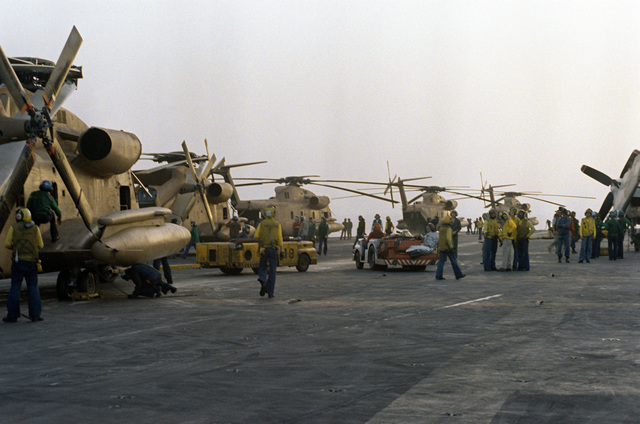 Crewmen perform last-minute preflight maintenance on RH-53 Sea Stallion helicopters parked on the flight deck of the nuclear-powered aircraft carrier USS NIMITZ (CVN-68). The helicopters are taking part in Operation Evening Light, a rescue mission to Iran