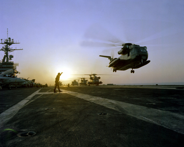 Operation Evening Light, a rescue mission to Iran, gets underway as an RH-53 Sea Stallion helicopter lifts off the flight deck of the nuclear-powered aircraft carrier USS NIMITZ (CVN-68). Other helicopters are lined up to be launched