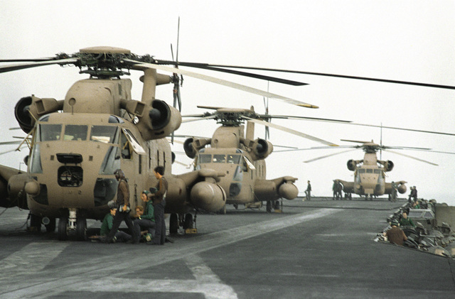 Three RH-53 Sea Stallion helicopters are lined up on the flight deck of the nuclear-powered aircraft carrier USS NIMITZ (CVN-68) in preparation for Operation Evening Light, a rescue mission to Iran
