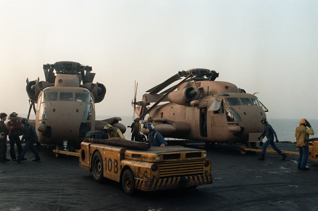 Tow tractors move two RH-53 Sea Stallion helicopters into position on the deck of the nuclear-powered aircraft carrier USS NIMITZ (CVN-68) prior to the start of Operation Evening Light, a rescue mission to Iran
