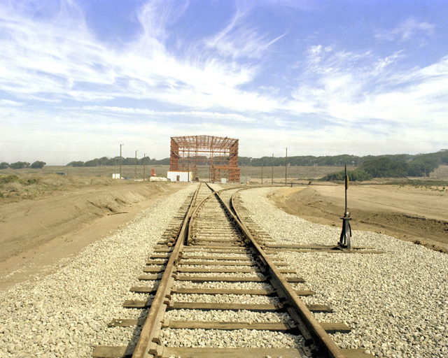 An east side view of the railroad tracks leading toward the partially constructed receipt and storage (RIS) building, a part of Space Launch Complex 6 (SLC-6)
