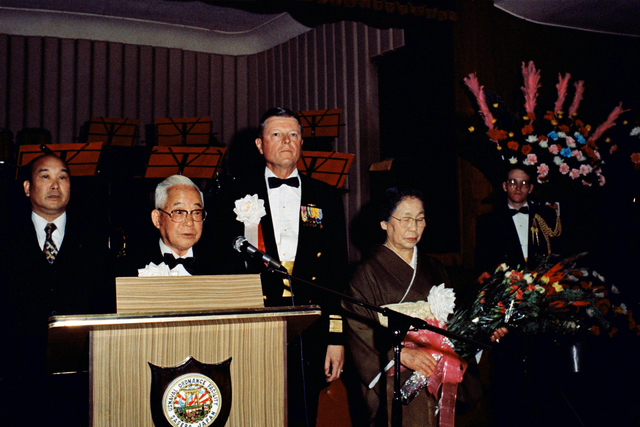 Mr. Shigeyasu Sakata, president of Shinwa Bank, the Japan-America Society and the Chamber of Commerce/Industry, addresses the crowd gathered for an award ceremony held in his honor.  Sakata received the Secretary of the Navy Distinguished Public Service Award for his efforts at building a cooperative spirit between the governments and peoples of the United States and Japan.  Rear Admiral (RADM) (upper half) Lando W. Zech, commander, US Naval Forces Japan, and Sakata's wife, Haru, look on