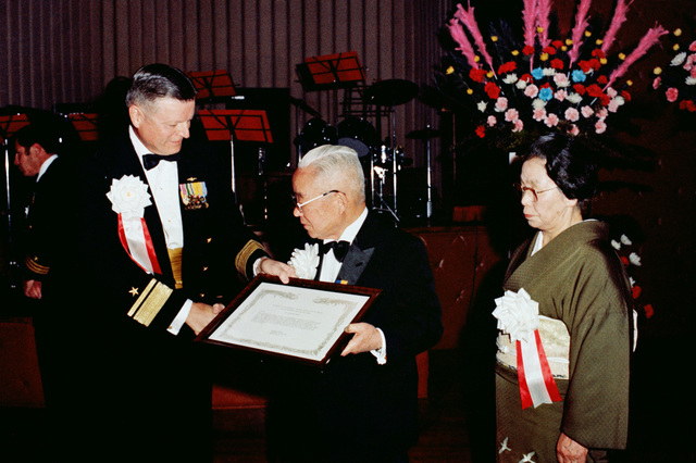 Rear Admiral (RADM) (upper half) Lando W. Zech, commander, US Naval Forces Japan, presents the Secretary of the Navy Distinguished Public Service Award to Mr. Shigeyasu Sakata, president of Shinwa Bank, the Japan-America Society and the Chamber of Commerce/Industry.  The award is in recognition of Sakata's efforts at building a cooperative spirit between the governments and peoples of the United States and Japan.  Sakata's wife, Haru, looks on