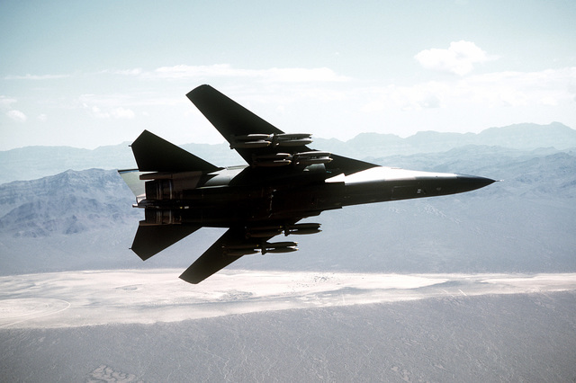 A bottom view of an F-111 aircraft banking to the left over the Nellis Air Force Base range. The aircraft, assigned to the 391st Tactical Fighter Training Squadron (TFTS), 366th Tactical Fighter Wing (TFW), is carrying 24 Mark 82 low-drag bombs