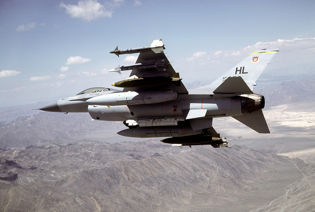 A left underside rear view of an F-16 Fighting Falcon aircraft banking to the right over Nellis Air Force Base. One AIM-9L Sidewinder, one AIM-9J Sidewinder, one 2,000-lb. Mark 84 bomb and an auxiliary fuel tank are on each wing. AN ALQ-119 electronic countermeasures pod is mounted on the centerline. The aircraft is assigned to the 4th Tactical Fighter Squadron, 388th Tactical Fighter Wing