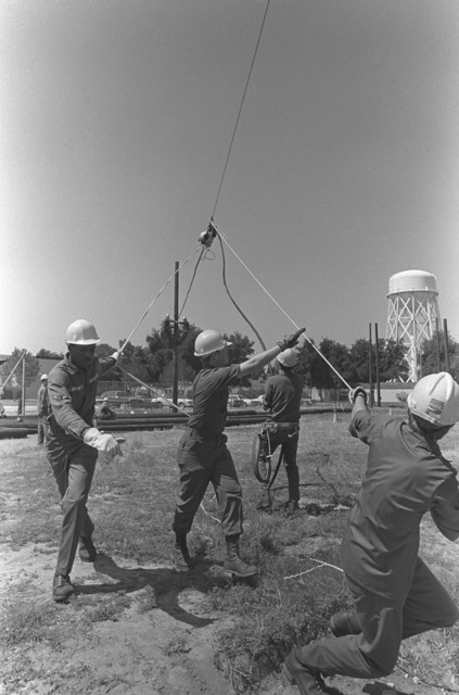 AIRMAN (AMN) Harry Mondor directs his crew of Air Force telephone linemen as they put up an aerial cable