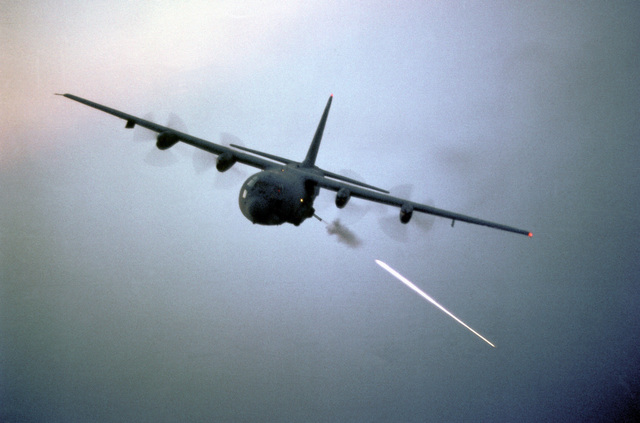 An air-to-air left front view of an AC-130 Hercules aircraft during target practice