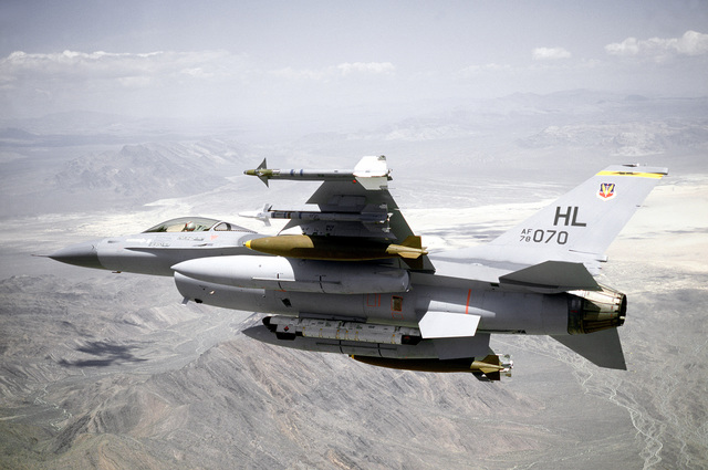 AN air-to-air left rear view of an F-16 Fighting Falcon aircraft banking to the right over a range. One AIM-9L Sidewinder, one AIM-9J Sidewinder, one 2,000-lb. Mark 84 bomb and an auxiliary fuel tank are on each wing. AN ALQ-119 electronic countermeasures pod is mounted on the centerline. The aircraft is assigned to the 4th Tactical Fighter Squadron, 388th Tactical Fighter Wing