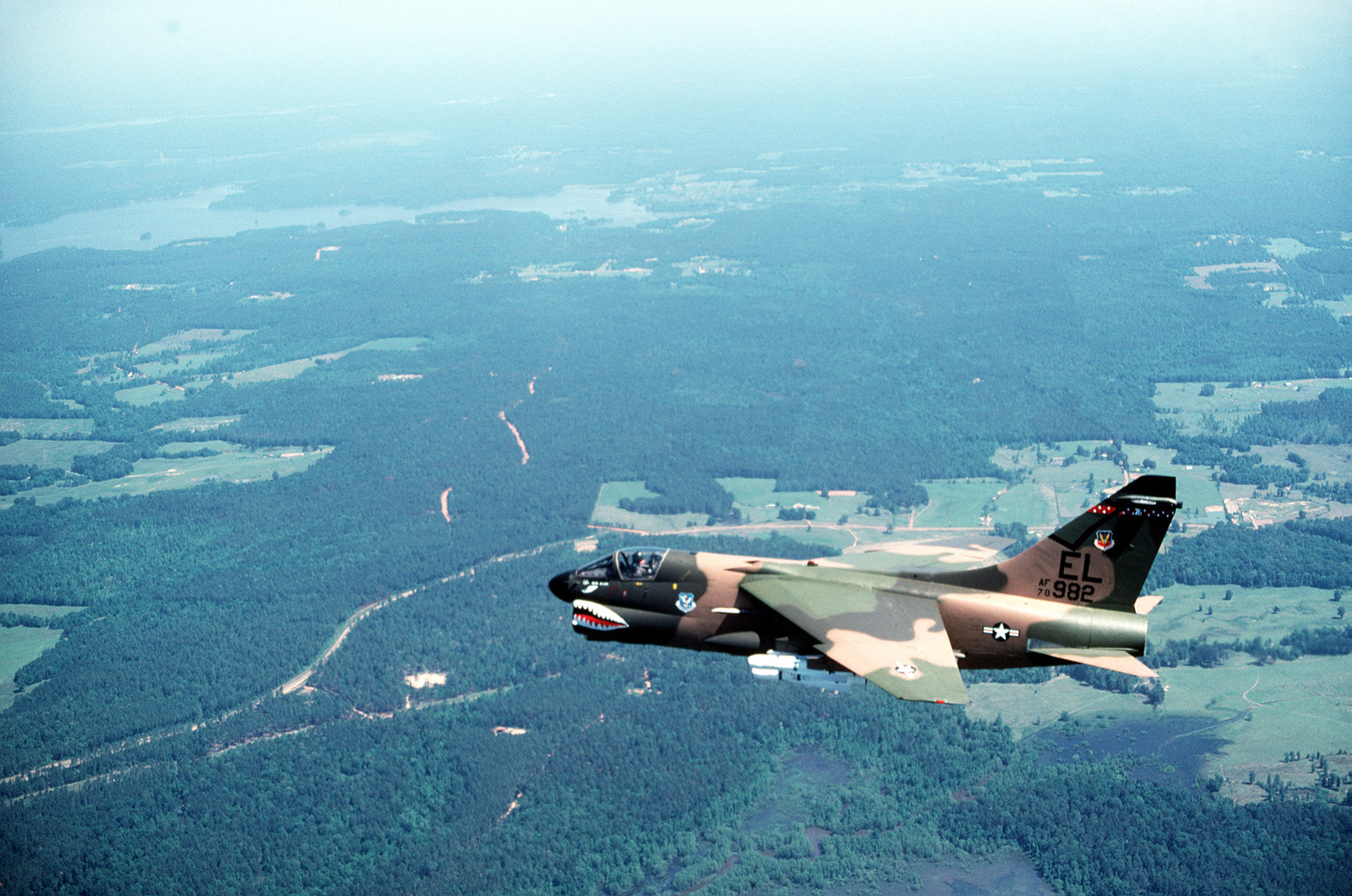 AN air-to-air left side view of an A-7D Corsair II aircraft over a range. Two AGM-65 Maverick missiles and one auxiliary fuel tank are on each wing. The aircraft is assigned to the 76th Tactical Fighter Squadron, 23rd Tactical Fighter Wing