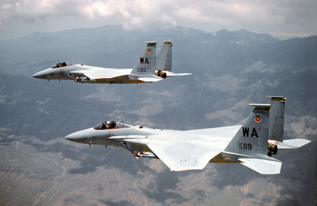 AN air-to-air left side view of two F-15 Eagle aircraft returning from a training mission. AN AIM-9L Sidewinder missile is mounted on the left wing of each aircraft. The aircraft are assigned to the 49th Tactical Fighter Wing