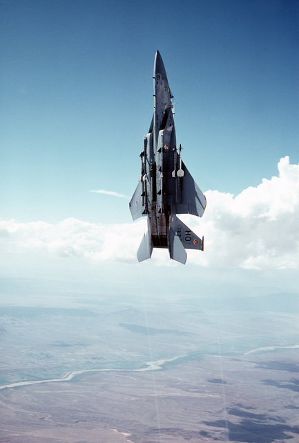 AN air-to-air low angle left view of an F-15 Eagle aircraft in a vertical climb over the White Sands Missile Range at Holloman Air Force Base. Two AIM-9 Sidewinder missiles are mounted on each wing and two AIM-7 Sparrow missiles are on each side of the fuselage. The aircraft is assigned to the 49th Tactical Fighter Wing