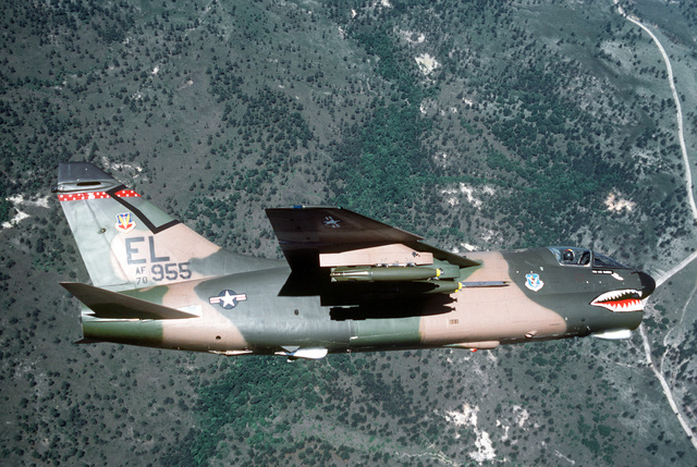 AN air-to-air right side view of an A-7D Corsair II aircraft over a range. Three Mark 82 high-drag bombs are on each wing. The aircraft is assigned to the 76th Tactical Fighter Squadron, 23rd Tactical Fighter Wing